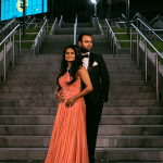Newly-wed couple posing against a flight of concrete stairs